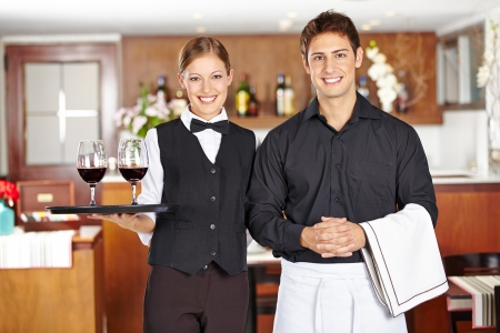 Team of waiter staff with wine glasses in a restaurant Stock Photo