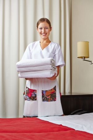 Hotel maid with fresh towels in a hotel room photo