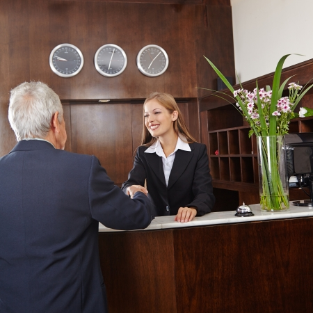 hotel service: Smiling receptionist in hotel giving handshake to senior guest