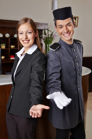 Smiling receptionist and happy bellboy in hotel offering a welcome photo
