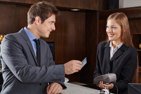 Business manager at hotel reception paying with credit card photo