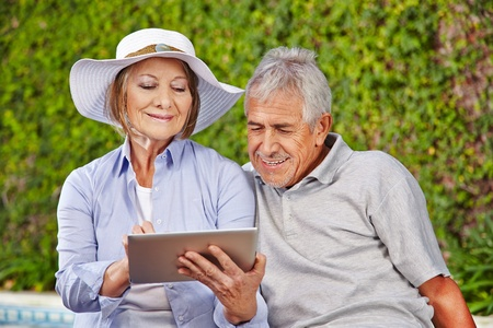 Two happy senior people sitting with tablet computer at pool photo