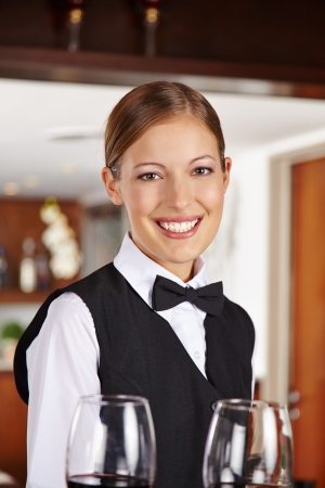 alcohol server: Happy waiter with two red wine glasses in hotel