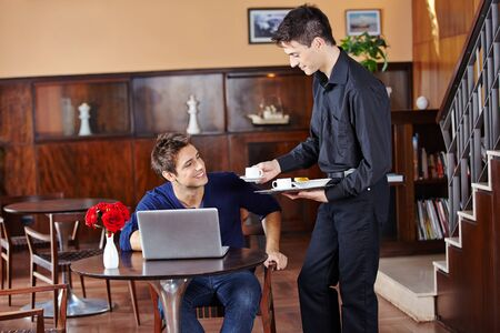 serve: Waiter offering coffee to man with laptop computer in a cafe