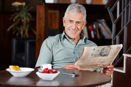 Happy senior man smiling at breakfast with newspaper photo