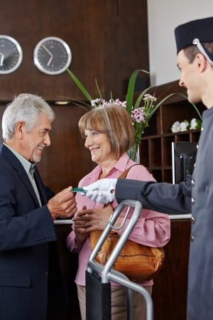 Senior couple getting key card in hotel from concierge Stock Photo - 20772961