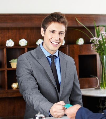 Friendly concierge working at check-in counter in hotel Stock Photo