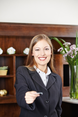 hotel staff: Smilinge female receptionist at hotel offering a key card Stock Photo