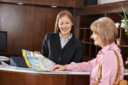 concierge: Senior woman in hotel looking at city map with female receptionist Stock Photo