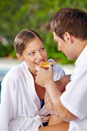 having breakfast: Young woman eating toast at pool of a hotel