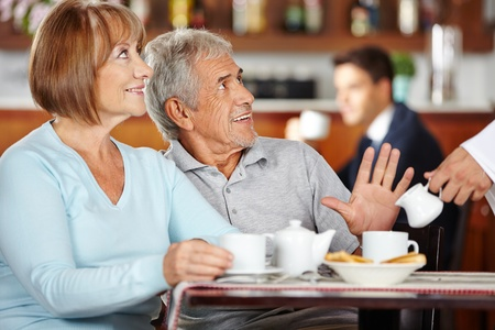 Senior man at breakfast rejecting coffee in a coffee shop photo