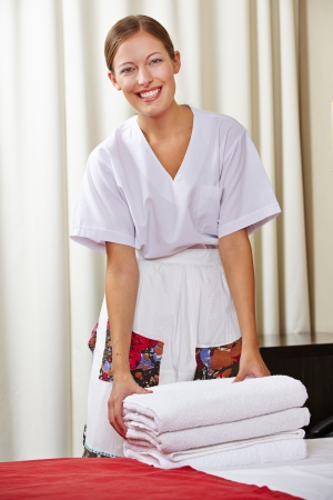 Portrait of a happy hotel maid doing housekeeping in a hotel room photo