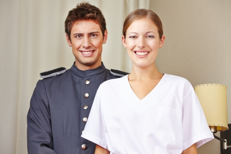 service occupation: Portrait of bellboy and hotel maid in a hotel room