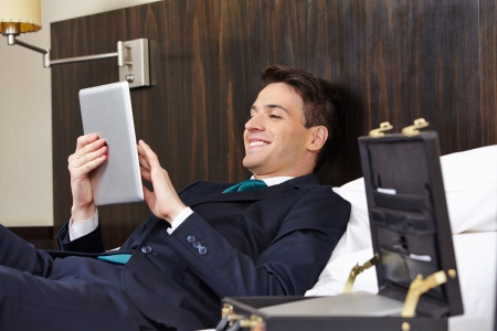 Successful business man working with tablet PC in his hotel room photo