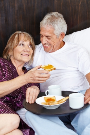 senior eating: Happy senior couple eating breakfast in bed in a hotel Stock Photo
