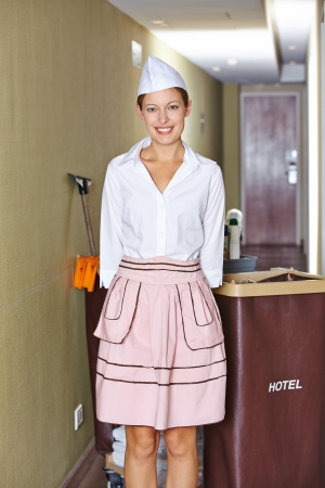 Portrait of happy hotel maid with a cleaning cart photo