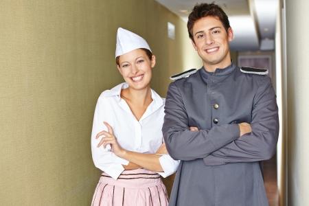 ama de llaves: Sonriente personal de servicio en el hotel, con sus brazos cruzados Foto de archivo