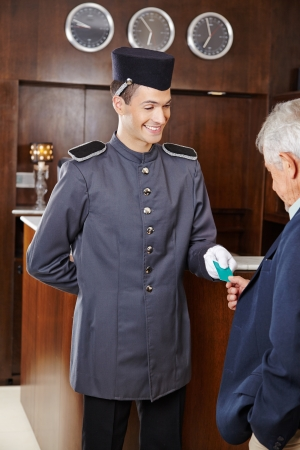 porter: Helpful concierge giving senior man his hotel key card Stock Photo