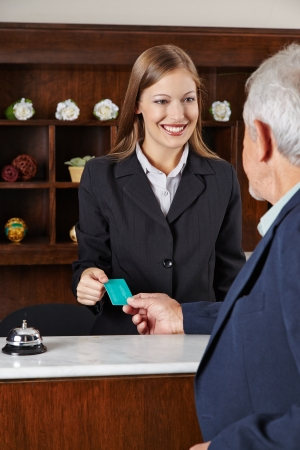 hotel staff: Smiling female receptionist in hotel greeting a senior man