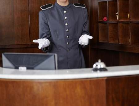 reception counter: Concierge with empty white gloves behind hotel reception counter