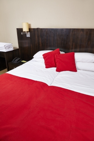 Clean red bed in a luxury hotel room photo