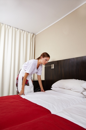 Young housekeeping maid cleaning bed in hotel room photo