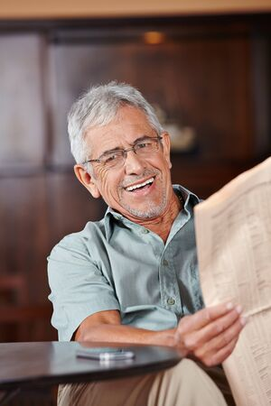 happy old people: Happy senior man with glasses reading newspaper in café