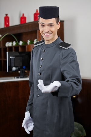 Happy concierge greeting guests in hotel on welcome Stock Photo - 20539310