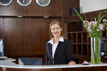 Happy female receptionist standing at hotel counter photo