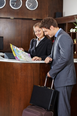 Guest with luggage looking at city map with hotel receptionist Stock Photo - 20778490