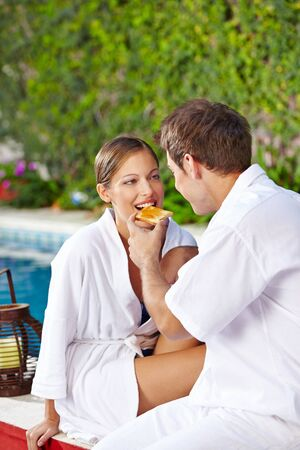 Happy couple having breakfast at hotel pool photo