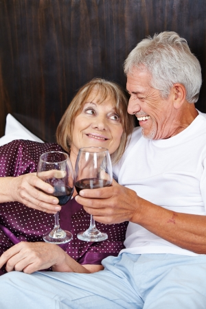 Senior couple in bed celebrating with red wine photo