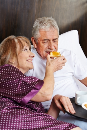 Happy elderly couple having breakfast together in a hotel bed photo