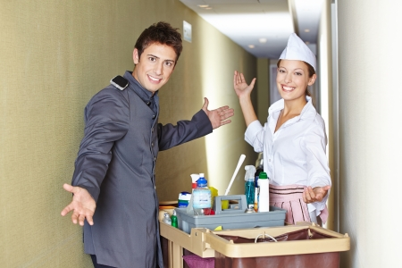 Concierge and hotel maid with cleaning cart in corridor photo