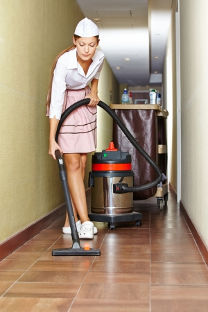 Cleaning lady with vacuum cleaner in hotel corridor photo