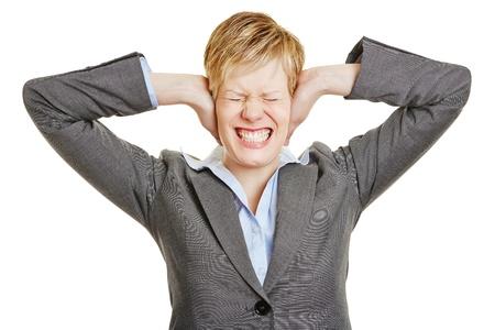 dolor de oido: Mujer de negocios tensionada tapándose los oídos con las manos Foto de archivo