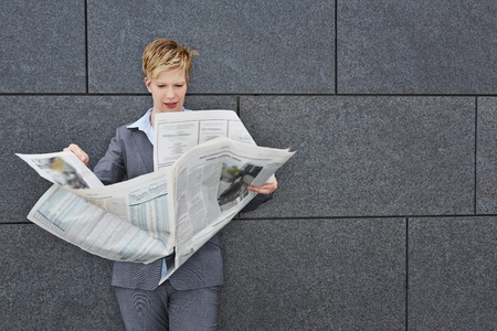 topicality: Business woman reading a daily newspaper in windy weather outdoors