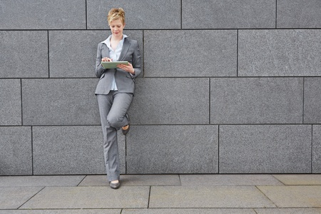 Business woman with tablet computer in the city leaning on a wall photo