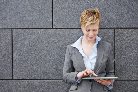 Young business woman using a tablet PC outdoors photo