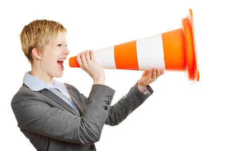 Young angry business woman screaming in a traffic cone photo