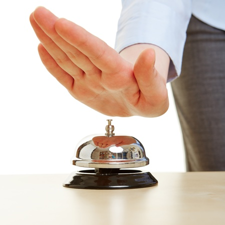 Hand on a hotel bell on a reception photo
