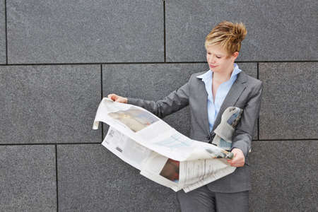 topicality: Business woman on the move holding a newspaper in windy weather Stock Photo