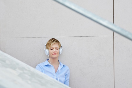 Young woman with headphones listening to music in urban city photo