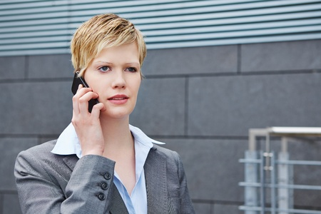 Young business woman using smartphone in city to make a phone call Stock Photo - 20970999