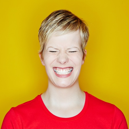 Grining young woman with her eyes closed on a yellow background photo