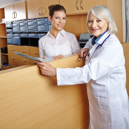 Elderly female doctor with receptionist at hospital reception photo