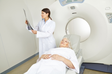 Doctor looking at x-ray image of senior patient at MRI therapy photo