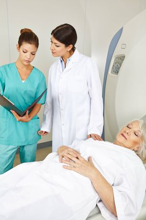 Doctor and nurse looking at medical records of senior patient at MRI photo