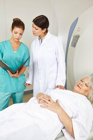 resonancia magnetica: Médico y enfermera mirando historias clínicas de paciente mayor en la RM