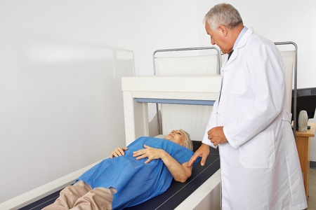 density: Doctor performing osteodensitometry in radiology to senior patient